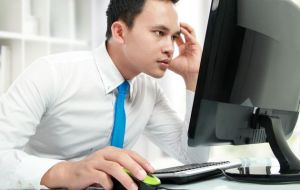 young man reading on computer free to use and share commercially on bing